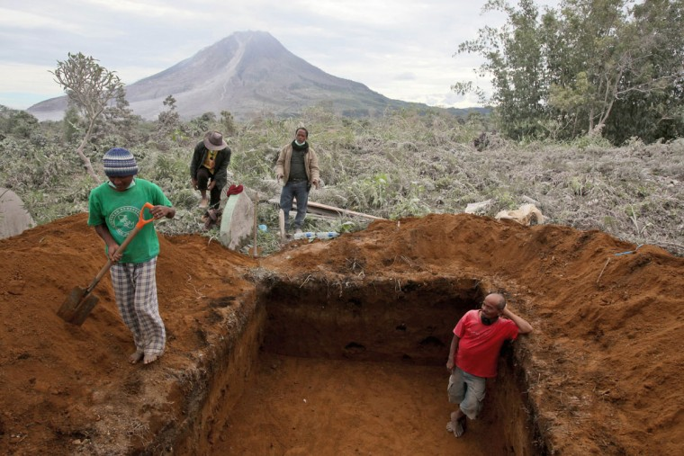 Workers prepare a grave for the victims in the eruption of Mount Sinabung in Sukandebi, North Sumatra, Indonesia, Sunday, May 22, 2016. The volcano blasted volcanic ash as high as 3 kilometers (2 miles) into the sky and down the slopes as far as 4.5 kilometers (3 miles), killing several people who were working on their farms. (AP Photo/Binsar Bakkara)