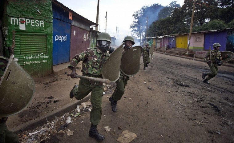 Kenyan police charge as they engage in running battles between police firing tear gas and protesters throwing rocks, in the Kibera slum of Nairobi, Kenya Monday, May 23, 2016. Kenya's police shot, beat and tear gassed opposition demonstrators across the country who tried to gather to call for the electoral commission to be dissolved due to allegations of bias and corruption. (AP Photo/Ben Curtis)