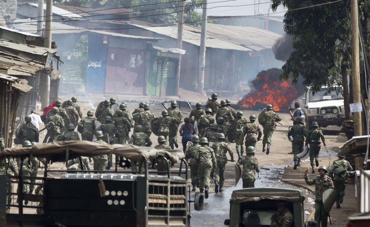 Kenyan policemen charge towards where protesters had lit a burning barricade, during running battles between police firing tear gas and protesters throwing rocks, in the Kibera slum of Nairobi, Kenya, Monday, May 23, 2016. Kenya's police shot, beat and tear gassed opposition demonstrators across the country who tried to gather to call for the electoral commission to be dissolved due to allegations of bias and corruption. (AP Photo/Ben Curtis)
