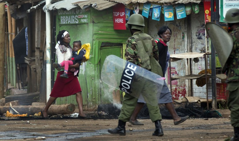 A woman takes advantage of a lull in the clashes to carry her baby to safety, as police firing tear gas engage protesters throwing rocks in the Kibera slum of Nairobi, Kenya Monday, May 23, 2016. Kenya's police shot, beat and tear gassed opposition demonstrators across the country who tried to gather to call for the electoral commission to be dissolved due to allegations of bias and corruption. (AP Photo/Ben Curtis)