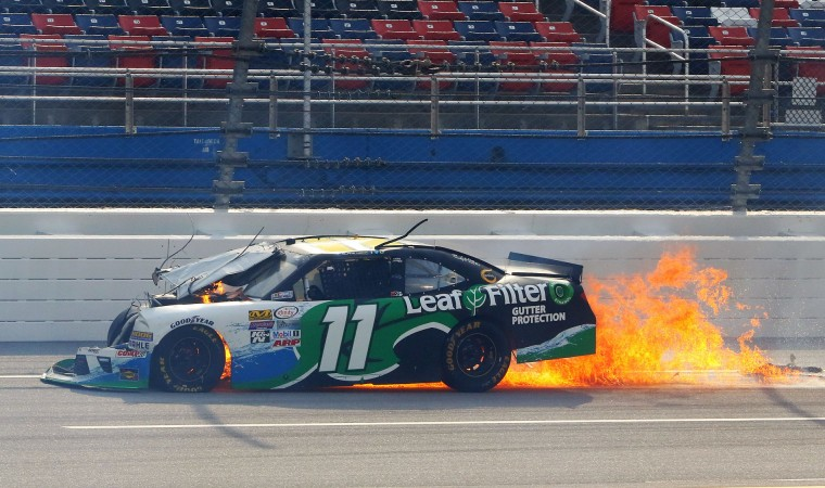 Blake Koch drives with the back of his car on fire after a wreck during the NASCAR Xfinity Series auto race at Talladega Superspeedway, Saturday, April 30, 2016, in Talladega, Ala. (AP Photo/Jay Alley)
