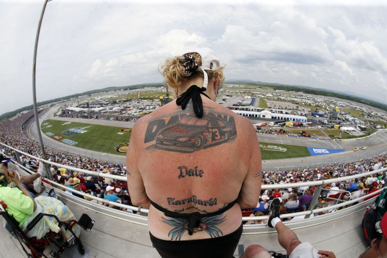 NASCAR fan Holli Ballien, of Mobile, Ala., shows off her tattoo of the late Dale Earnhardt during NASCAR Xfinity Series auto race at Talladega Superspeedway, Saturday, April 30, 2016, in Talladega, Ala. (AP Photo/John Bazemore)