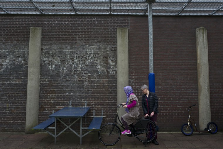 A Dutch volunteer teaches an Afghan refugee woman how to ride a bicycle at a yard in the former prison of De Koepel in Haarlem, Netherlands. With crime declining in the Netherlands, the country is looking at new ways to fill its prisons. (AP Photo/Muhammed Muheisen)