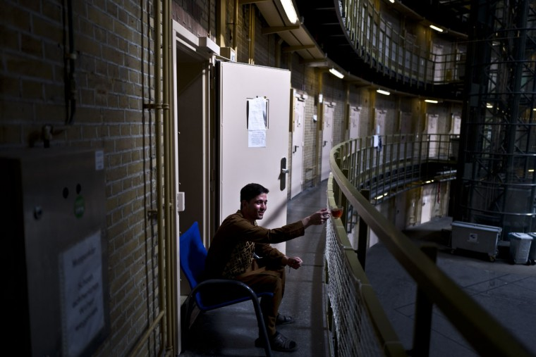 Afghan refugee Siratullah Hayatullah, 23, drinks tea by the doorway of his room at the former prison of De Koepel in Haarlem, Netherlands. (AP Photo/Muhammed Muheisen)