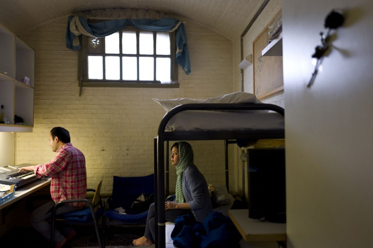 Afghan refugee Hamed Karmi, 27, plays keyboard next to his wife Farishta Morahami, 25, sitting on a bed inside their room at the former prison of De Koepel in Haarlem, Netherlands. The government has let Belgium and Norway put prisoners in its empty cells and now, amid the huge flow of migrants into Europe, several Dutch prisons have been temporarily pressed into service as asylum seeker centers. (AP Photo/Muhammed Muheisen)