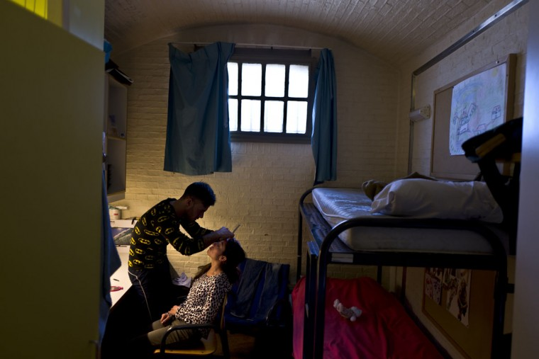 Yazidi refugee Yassir Hajji, 24, from Sinjar, Iraq, adjusts the eyebrow of his wife Gerbia,18, at their room in the former prison of De Koepel in Haarlem, Netherlands. (AP Photo/Muhammed Muheisen)