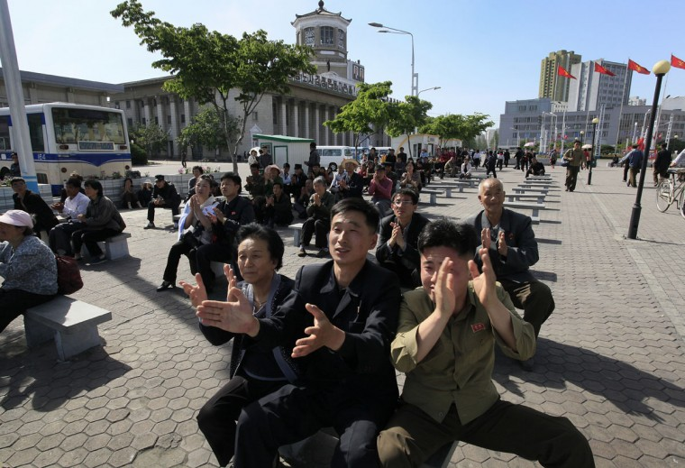 North Koreans clap as they listen to North Korean leader Kim Jong Un speak at the party congress during a television broadcast on a public screen near the Pyongyang train station on Sunday, May 8, 2016, in Pyongyang, North Korea. North Korean leader Kim Jong Un said during a critical ruling party congress that his country will not use its nuclear weapons first unless its sovereignty is invaded, state media reported. (AP Photo/Kim Kwang Hyon)