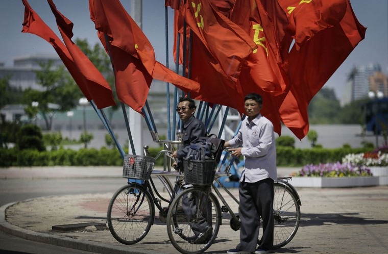 North Korean men wait with their bicycles to cross a street decorated with flags of their ruling Workers' Party Saturday, May 7, 2016 in Pyongyang, North Korea. North Korean leader Kim Jong Un hailed his country's recent nuclear test to uproarious applause as he convened the first full congress of its ruling party since 1980, an event intended to showcase the North's stability and unity in the face of tough international sanctions and deepening isolation. (AP Photo/Wong Maye-E)