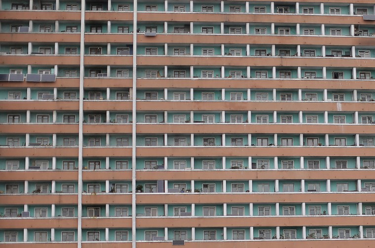 A woman stands in her balcony of an apartment building on Friday, May 6, 2016, in Pyongyang, North Korea. North Korea on Friday opened the first full congress of its ruling party since 1980, a major political event intended to showcase the country's stability and unity under young leader Kim Jong Un despite international criticism and tough new sanctions over the North's recent nuclear test and a slew of missile launches. (AP Photo/Wong Maye-E)