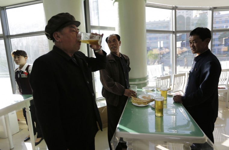 "In this Saturday, May 7, 2016, photo, Pak Sun Won, 66, left, a retired physician drinks a glass of draft beer at the Taedonggang Beer shop with his friends in Pyongyang, North Korea. Ahead of the ongoing congress of North Korea's ruling Workers' Party, the nation was called upon to do massive overtime to boost production and show their devotion to leader Kim Jong Un in a 70-day ""loyalty campaign."" And that's in addition to the hour after hour of rehearsals for huge rallies when their ruling party wraps up its first congress in decades. So how does a tired North Korean unwind? Beer. Beer. And more beer. (AP Photo/Wong Maye-E)"