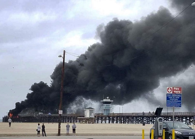 This photo provided by Amy Stanton shows a large plum of smoke from a fire burning on the Seal Beach pier in Seal Beach, Calif. on Friday, May 20, 2016. A fire is burning on a former restaurant on Southern California's Seal Beach Pier. The blaze erupted early Friday at the end of the long wooden pier southeast of Los Angeles. Harbor patrol boats are attacking the flames with streams from water cannons while firefighters direct streams from hoses on the pier. (Amy Stanton via AP)