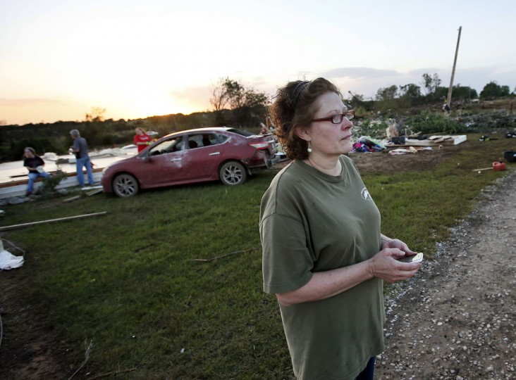 Lisa Buckner stands in front of where her home used to be as friends and family help to clean up after her home was destroyed by a tornado west of Wynnewood, Okla., in rural Gavin County, Monday, May 9, 2016. Storms swept through the nation's midsection Monday, spawning numerous tornadoes. (Nate Billings/The Oklahoman via AP)