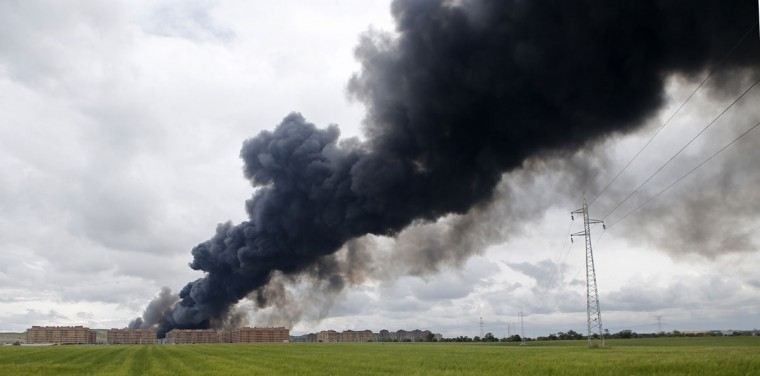 Billowing black smoke rises from behind large housing blocks in Sesena, central Spain, Friday, May 13, 2016. A massive fire is raging at a sprawling tire dump in a town near Madrid, sending a spectacular cloud of thick black smoke into the air that's visible for at least 30 kilometers (20 miles). Ten teams of firefighters are trying to put out the blaze at the tire dump in the town of Sesena, still raging more than 10 hours after it started. (AP Photo/Paul White)