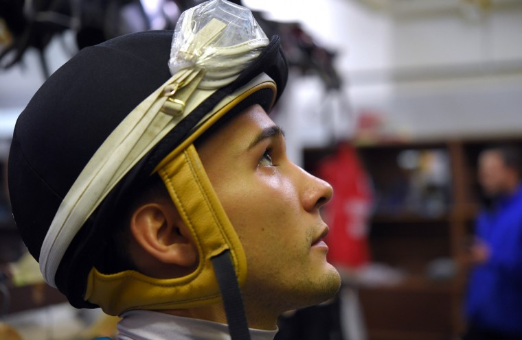 Nik watches the previous race on a television in the jockey's room. (Lloyd Fox/Baltimore Sun)