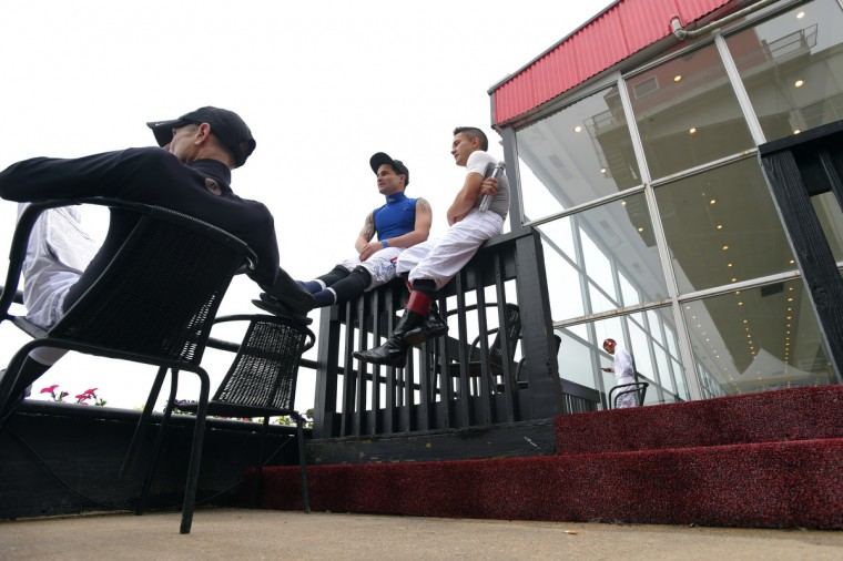 Nik Juarez and other jockeys watch races from the jockey's viewing stand as they wait for their races. (Lloyd Fox/Baltimore Sun)