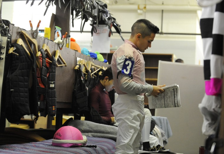 Nik Juarez a third generation jockey studies the racing program before each race to know what to expect from other horses.     (Lloyd Fox/Baltimore Sun)