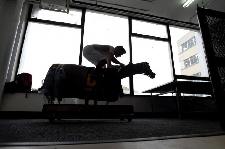 Nik Juarez rides an exersizer outside of the jockey's room as he wars up for a race. (Lloyd Fox/Baltimore Sun)