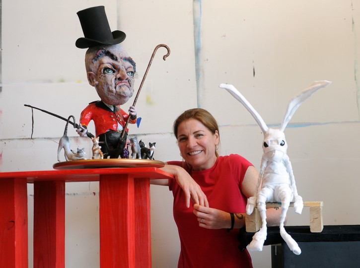 "Tiffany Lange, founder of Charm City Puppets, poses with some of her creations at her studio in the Creative Alliance at the Patterson. On left is a sculpture called ""The Cat Herder."" On right, a sad bunny. (Barbara Haddock Taylor/Baltimore Sun)"