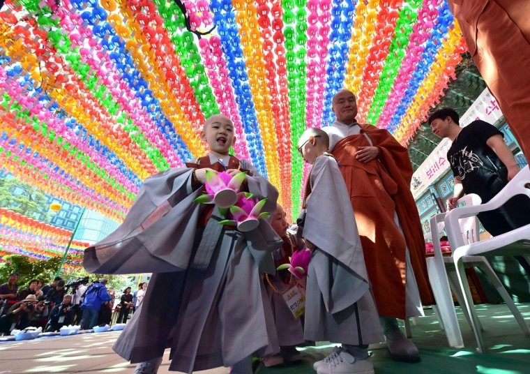 South Korean young novice monks stand under lotus lanterns after having their heads shaved during a ceremony entitled 'Children Becoming Buddhist Monks', at the Jogye temple in Seoul on May 2, 2016. (JUNG YEON-JE/AFP/Getty Images)