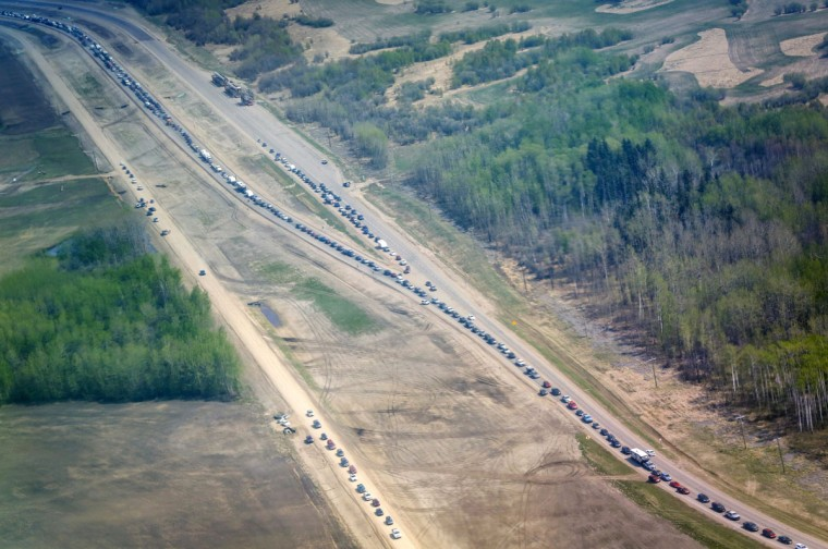 Traffic is at a standstill on Highway 63 heading south as residents flee with wildfires burning in and around Fort McMurray, Alberta, Wednesday, May 4, 2016. The raging wildfire emptied Canada's main oil sands city, destroying entire neighborhoods of Fort McMurray, where officials warned Wednesday that all efforts to suppress the fire have failed. (Jeff McIntosh/The Canadian Press via AP)