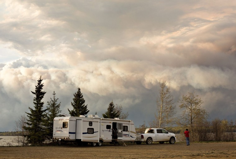 Evacuees camp by a lake as smoke fills the sky near Fort McMurray, Alberta, on Wednesday, May 4, 2016. Alberta declared a state of emergency Wednesday as crews frantically held back wind-whipped wildfires. No injuries or fatalities have been reported. (Jason Franson/The Canadian Press via AP)