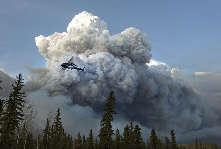 A helicopter flies past a wildfire in Fort McMurray, Alberta on Wednesday, May 4, 2016. Alberta declared a state of emergency Wednesday as crews frantically held back wind-whipped wildfires that have already torched homes and other buildings in Canada's main oil sands city of Fort McMurray, forcing thousands of residents to flee. (Jason Franson /The Canadian Press via AP)