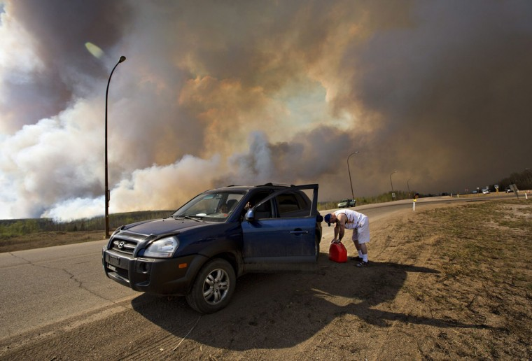 An evacuee puts gas in his car on his way out of Fort McMurray, Alberta, as a wildfire burns in the background Wednesday, May 4, 2016. The raging wildfire emptied Canada's main oil sands city, destroying entire neighborhoods of Fort McMurray, where officials warned Wednesday that all efforts to suppress the fire have failed. (Jason Franson /The Canadian Press via AP)