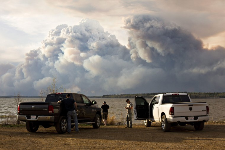 Evacuees watch the wildfire near Fort McMurray, Alberta, on Wednesday, May 4, 2016. Alberta declared a state of emergency Wednesday as crews frantically held back wind-whipped wildfires. No injuries or fatalities have been reported. (Jason Franson/The Canadian Press via AP)