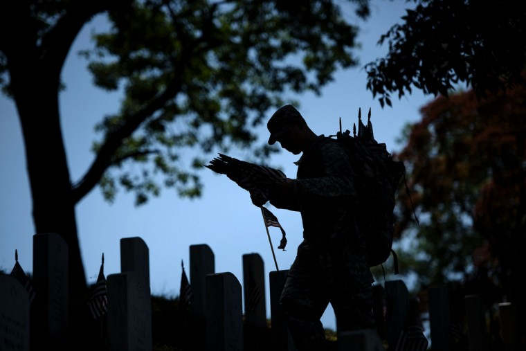 A soldier places American flags at graves in Arlington National Cemetery on May 26, 2016 in Arlington, Virginia in preparation for Memorial Day. (BRENDAN SMIALOWSKI/AFP/Getty Images)