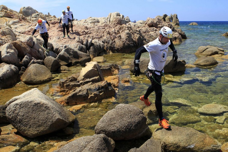 Racers run on rocks during a coastering session during the 20th Corsica Raid race in Porticcio along the Gulf of Ajaccio on June 8, 2016 on the French island of Corsica. (PASCAL POCHARD-CASABIANCA/AFP/Getty Images)