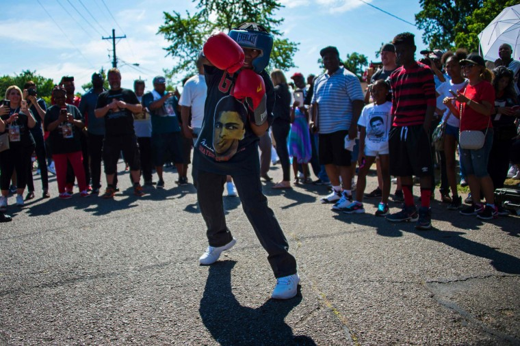 Thirteen-year-old Malik Parker shadow boxes outside boxing legend Muhammad Ali's childhood home where mourners wait to pay their respects during a funeral procession on June 10, 2016 in Louisville, Kentucky. Thousands of people from near and far were expected to line the streets of Muhammad Ali's hometown Louisville on Friday to say goodbye to the boxing legend and civil rights hero, who mesmerized the world with his dazzling skills. (Jim Watson/AFP/Getty Images)
