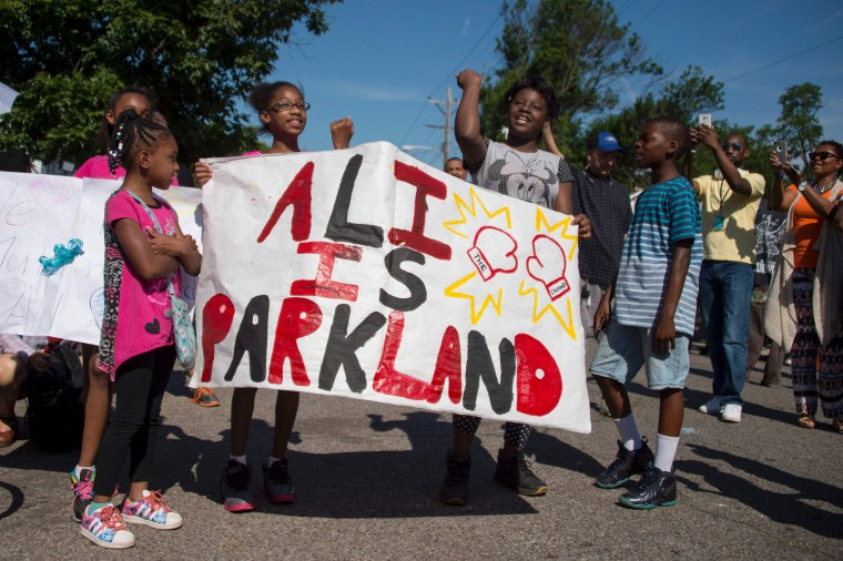 Children chant and hold up placards outside boxing legend Muhammad Ali's childhood home where mourners wait to pay their respects during a funeral procession on June 10, 2016 in Louisville, Kentucky. Thousands of people from near and far were expected to line the streets of Muhammad Ali's hometown Louisville on Friday to say goodbye to the boxing legend and civil rights hero, who mesmerized the world with his dazzling skills. (Jim Watson/AFP/Getty Images)