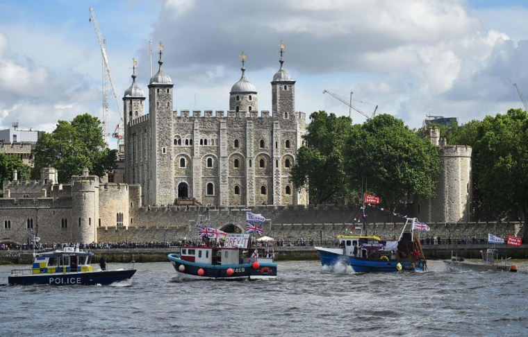 Fishing boats campaigning for Brexit sail by the Tower of London in London on June 15, 2016. A Brexit flotilla of fishing boats sailed up the River Thames into London today with foghorns sounding, in a protest against EU fishing quotas by the campaign for Britain to leave the European Union. (AFP PHOTO / BEN STANSALL)