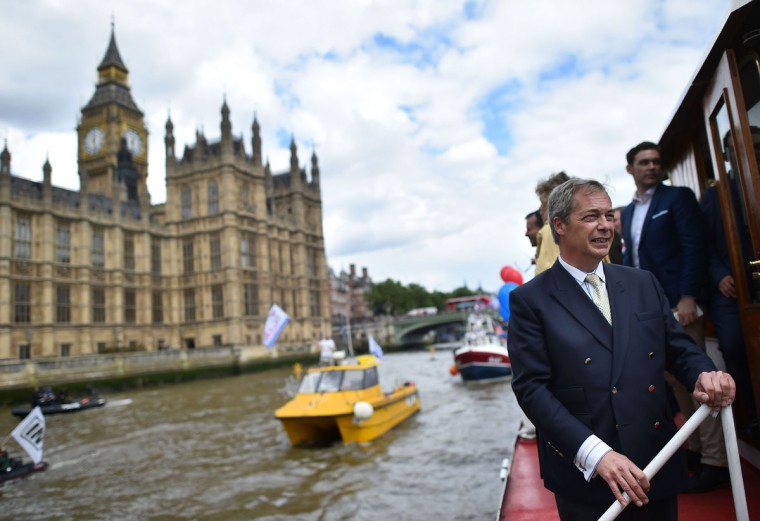 A boat carrying supporters for the Remain in the EU campaign including Sir Bob Geldoff (C) shout and wave at Brexit fishing boats as they sail up the river Thames in central London on June 15, 2016. A Brexit flotilla of fishing boats sailed up the River Thames into London today with foghorns sounding, in a protest against EU fishing quotas by the campaign for Britain to leave the European Union. (AFP PHOTO / BEN STANSALL)