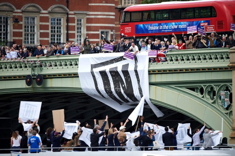 Campaigners to remain in the EU unfurl a banner on Westminster Bridge as they wait for a flotilla of boats from the group 'Fishing for Leave' to sail by on the river Thames in London on June 15, 2016. A Brexit flotilla of fishing boats sailed up the River Thames into London today with foghorns sounding, in a protest against EU fishing quotas by the campaign for Britain to leave the European Union. (AFP PHOTO / Niklas HALLE'N)