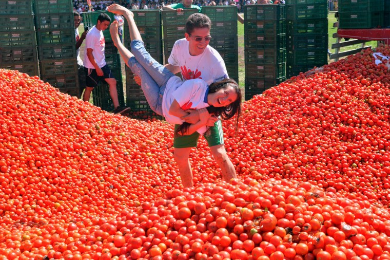 "A couple participates in the 10th annual tomato fight festival, known as ""tomatina"", in Sutamarchan, Boyaca department, Colombia, on June 5, 2016. (GUILLERMO LEGARIA/AFP/Getty Images)"