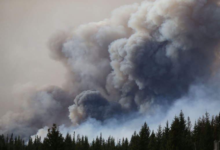 FILE -- This file photo taken on May 7, 2016 shows flames and smoke rising off Highway 63 outside Fort McMurray, Canada. Mandatory evacuation orders were issued for some 20 oil sands camps and facilities in Canada's Alberta province due to smoke and flames from the Fort McMurray wildfire, regional emergency officials said May 17, 2016. The evacuation orders, which affect some 8,000 people, were issued late Monday (0200 GMT Tuesday) for a region between Fort McMurray and a few kilometers south of the town of Fort MacKay, officials said. (Cole Burston/AFP/Getty Images)