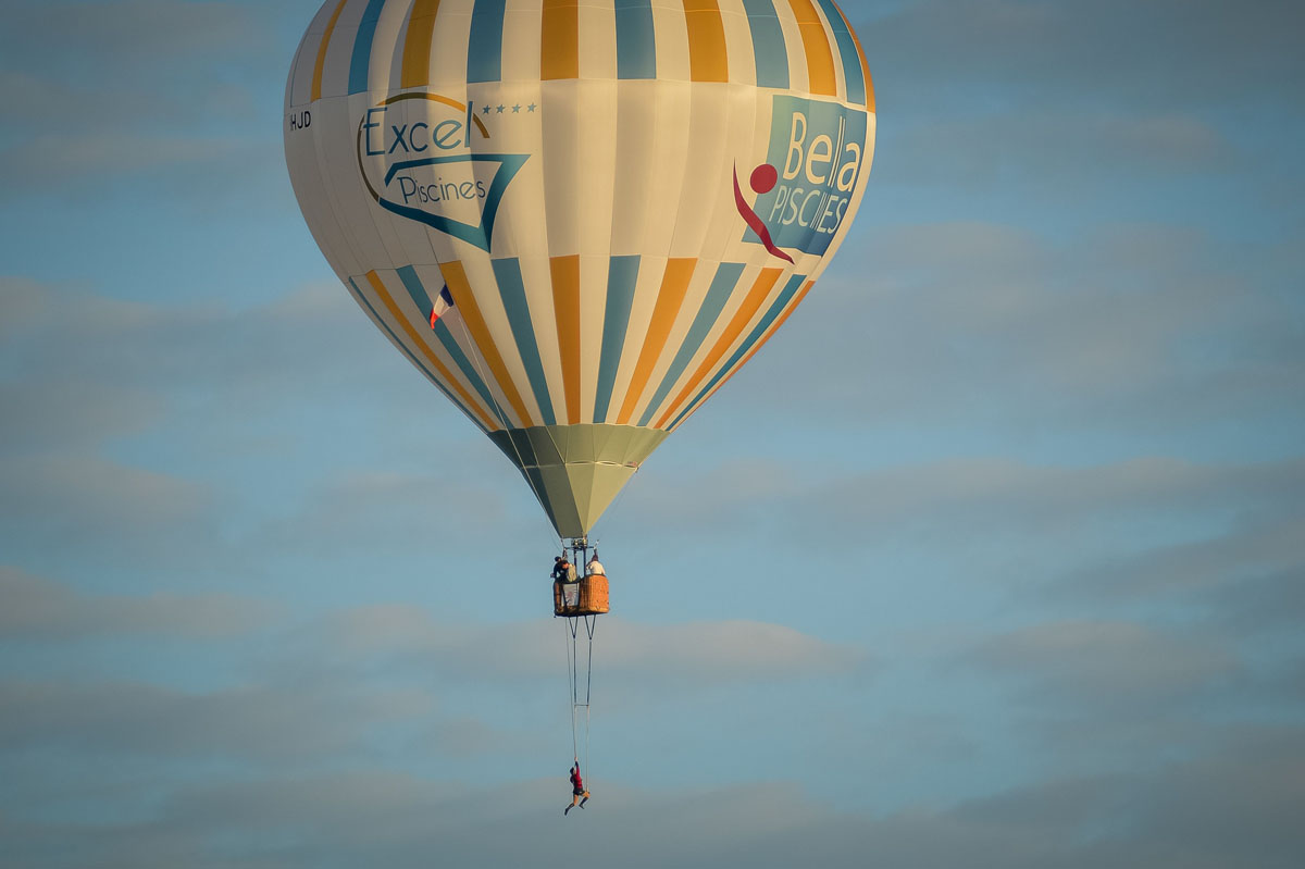 French artist floats through the air on a balloon trapeze