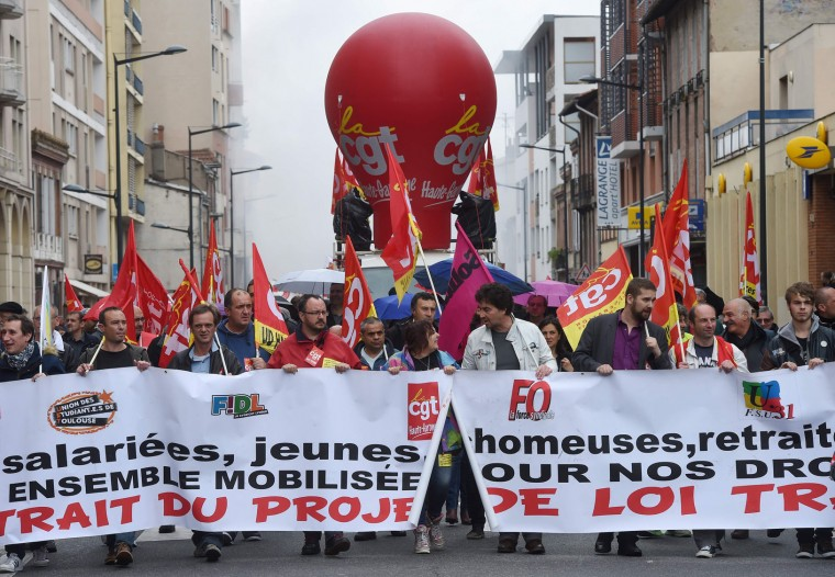 "Protestors holding French CGT union's flags hold a banner reading ""Withdrawal of the draft law"" as they march on June 2, 2016 in Toulouse, southern France, during a demonstration against the government's planned labour law reforms. Eight policemen were lightly wounded during a clash with protesters blocking a ring road in Toulouse, as France suffered a third day of rail strikes in opposition to the Socialist government's new labour reforms that have sparked three months of often violent protests. (Eric Cabanis/AFP/Getty Images)"