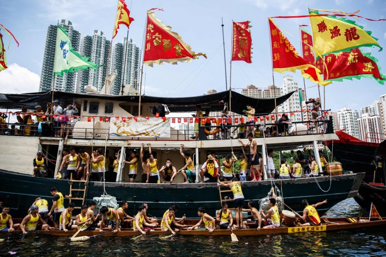 Teammates rest on their host ship above their dragon boat (bottom) during races held to celebrate the Tuen Ng festival in Hong Kong on June 9, 2016. (Anthony Wallace/AFP/Getty Images)