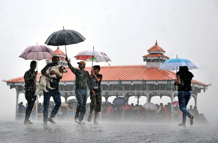 Indian pedestrians carry a dog as they make their way past others sheltering in a pavilion during a heavy monsoon rain downpour in Shimla on June 22, 2016. At least 93 people have been struck by lightning and killed in India over the past two days, disaster management officials said, as annual monsoon rains swept the country. Lightning strikes are relatively common in India during the June-October monsoon, which hit the southern coast earlier this month, but this week's toll is particularly high. (Str/AFP/Getty Images)