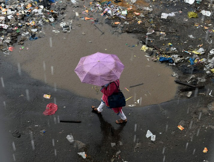 An Indian officegoer walks during a downpour in Mumbai on June 20, 2016. Annual monsoon rains have progressed to parts of western and central India, easing fears of millions of desperate farmers after two straight years of drought, the weather department said. Farmers rely on the monsoon rains, which hit the Kerala coast every year and then sweep across the country, to water their crops and replenish dams and reservoirs. The arrival of the monsoon is always keenly watched in India, but even more so this year as much of the country reels from the drought. (Indranil Mukherjee/AFP/Getty Images)
