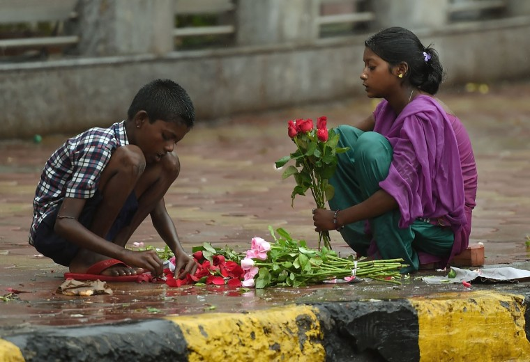 Indian girl children sort through roses for sale during rain showers in Mumbai on June 28, 2016. Annual monsoon rains have progressed to most parts of western and central India, easing fears of millions of desperate farmers after two straight years of drought, the weather department said. (Punit Paranjpe/AFP/Getty Images)