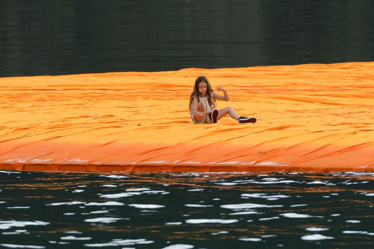 "A girl laces her shoes as she sits on the monumental installation ""The Floating Piers"" created by Artist Christo Vladimirov Javacheff and Jeanne-Claude, on June 16, 2016 during a press preview at the lake Iseo, northern Italy. (FILIPPO MONTEFORTE/AFP/Getty Images)"