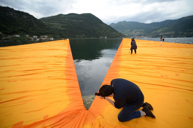 "A man takes pictures of the monumental installation ""The Floating Piers"" created by Artist Christo Vladimirov Javacheff and Jeanne-Claude, on June 16, 2016 during a press preview at the lake Iseo, northern Italy. (FILIPPO MONTEFORTE/AFP/Getty Images)"