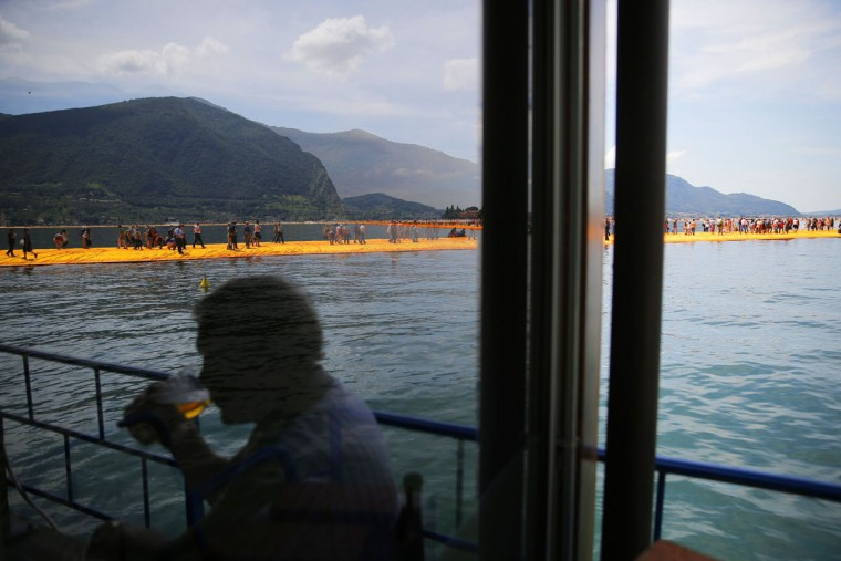A person is reflected in a glass door as people walk on the monumental installation entitled 'The Floating Piers' created by artist Christo Vladimirov Javacheff on Iseo Lake, in northern Italy, on June 18, 2016. (MARCO BERTORELLO/AFP/Getty Images)