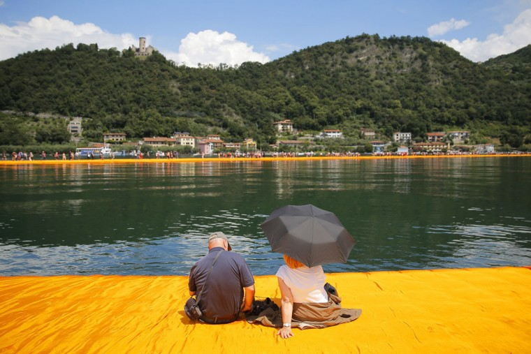 A couple sits with an umbrella on the monumental installation entitled 'The Floating Piers' created by artist Christo Vladimirov Javacheff on Iseo Lake, in northern Italy, on June 18, 2016. (MARCO BERTORELLO/AFP/Getty Images)