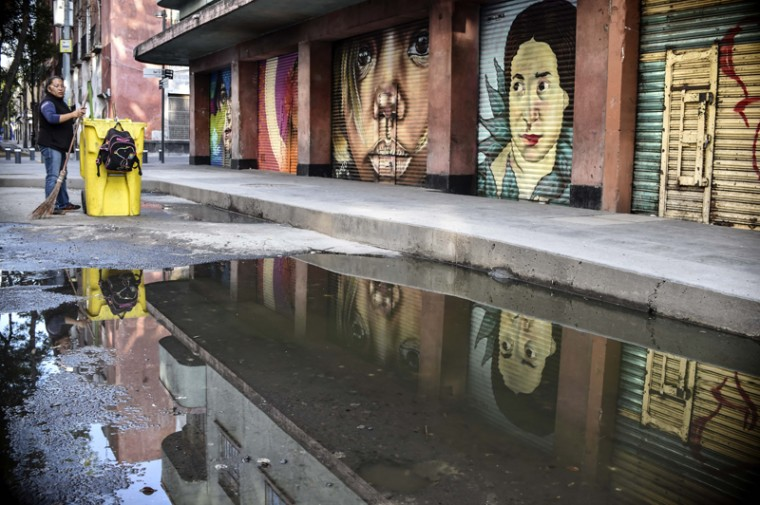 A municipal employee cleans the street Tuesday next to murals painted as part of a program of the municipality that aims at rescuing public spaces of the historic center in Mexico City.(YURI CORTEZ/AFP/Getty Images)