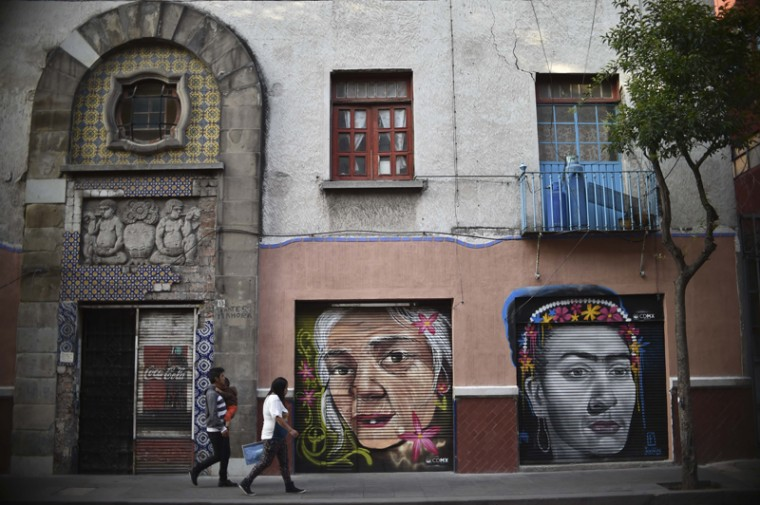 Pedestrians walk past murals Tuesday. The painting are part of a series aimed at rescuing public spaces in Mexico City's historic center. (YURI CORTEZ/AFP/Getty Images)