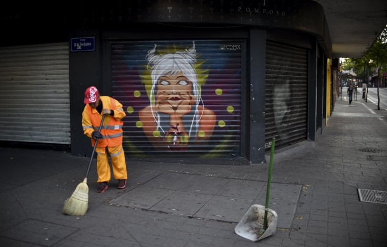 A municipal employee sweeps Tuesday near one of the murals painted as part of a program to improve public spaces in Mexico City's historic center. (YURI CORTEZ/AFP/Getty Images)